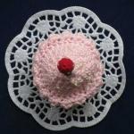 Kleiner  Schokokuchen mit rosa Zuckerüberzug und Kirsche.