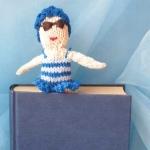 Petra Oellingers Lesedaeumling Badenixe blau: Sie trägt einen blauem Badeanzug und eine Badehaube aus blauen Blüten, ist zirka zehn Zentimeter groß und kann als Lesezeichen verwendet werden.